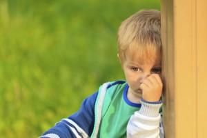 Niño escondido tras una esquina