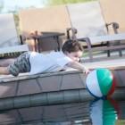 Niño jugando junto a una piscina
