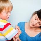 Madre curando una herida a un hijo