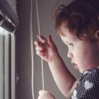 Niño tirando del cordón de una persiana