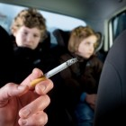 Niño recibiendo humo de tabaco dentro del coche
