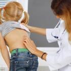 Pediatra explorando la espalda de una niña