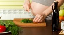 Mujer embarazada picando verduras