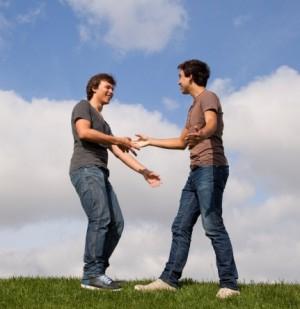 Dos chicos adolescentes dándose la mano