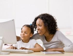 Niña usando un ordenador junto a un adulto