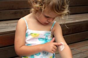 Niña con dermatitis aplicándose una crema