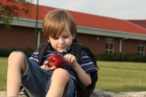 Niño tomando una manzana en el patio del colegio