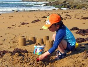Niño jugando en la playa protegido del sol
