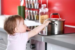 niño pequeño cogiendo un cazo mientras se cocina