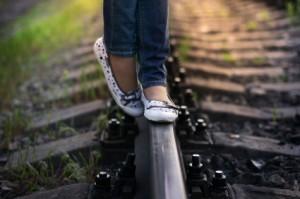 Pies de una niña sobre la vía del tren
