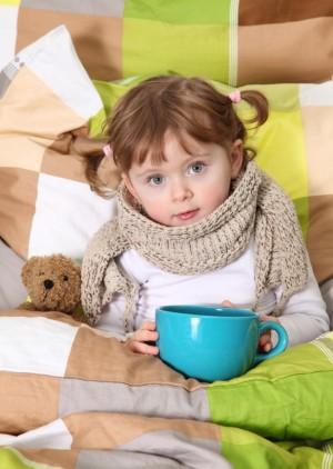 Niña con gripe tomando una infusión