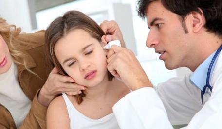 Pediatra explorando el oído de una niña
